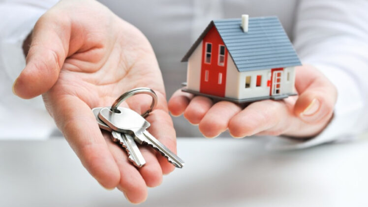 A Person Having A Homekit In One Hand A Key In Other Hand Representing Mortgage Loan Concept.