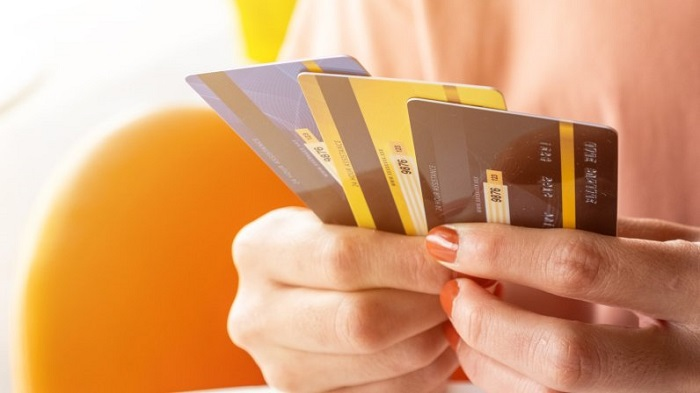 A Woman Hold A Collection Of Credit Cards In Her Hand.