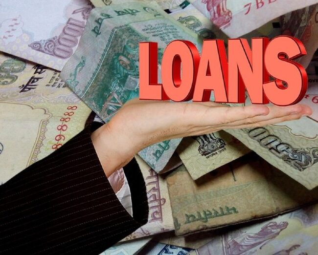 An image representing the term LOAN placed on a palm, on top of currencies